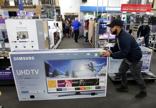 (AP Photo/Charlie Riedel, File). FILE - In this Nov. 23, 2017, file photo, Jesus Reyes pushes a television down an aisle as he shops at a Best Buy store in Overland Park, Kan. Just before the Super Bowl, retailers normally discount their selections of ...