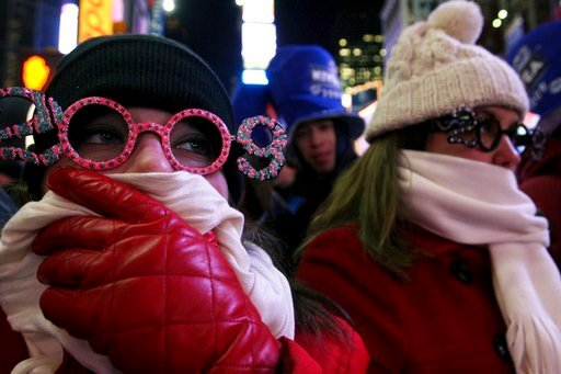 (AP Photo/Tina Fineberg, File). In this Dec. 31, 2008 file photo, Allison Smith of Jacksonville, Fla, left, tries to keep warm as she and others take part in the New Year's Eve festivities in New York's Times Square.
