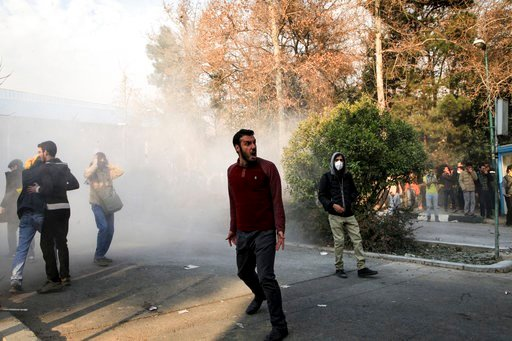 (AP Photo). In this photo taken by an individual not employed by the Associated Press and obtained by the AP outside Iran, university students attend a protest inside Tehran University while a smoke grenade is thrown by anti-riot Iranian police, in Teh...