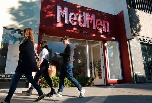 (AP Photo/Richard Vogel, File). FILE - In this Thursday, Dec. 21, 2017, file photo pedestrians walk past MedMen a marijuana dispensary in Los Angeles. Californians may awake on New Year's Day to a familiar scent in greater-than-normal concentrations. A...