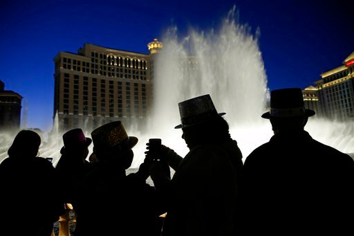 (AP Photo/John Locher, File). FILE - In this Dec. 31, 2015, file photo, people watch the fountains at the Bellagio while wearing paper hats to celebrate New Years Eve in Las Vegas. Tens of thousands of revelers will ring in the New Year in Las Vegas un...