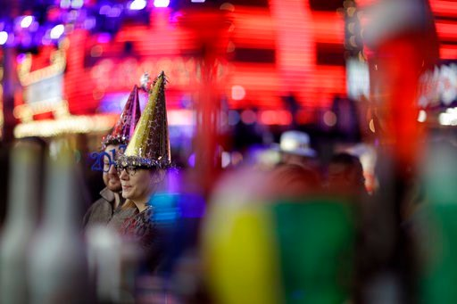 (AP Photo/John Locher, File). FILE - In this Dec. 31, 2016, file photo, People attend a New Year's Eve celebration in Las Vegas. Tens of thousands of revelers will ring in the New Year in Las Vegas under the close eye of law enforcement just three mont...