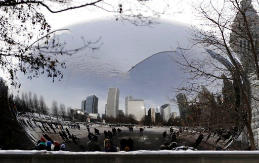 (AP Photo/Nam Y. Huh). People visit a snow-covered Cloud Gate at Millennium Park in Chicago, Sunday, Dec. 31, 2017.