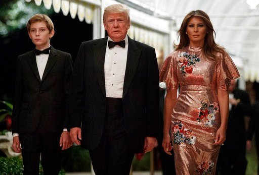 (AP Photo/Evan Vucci). President Donald Trump arrives for a New Year's Eve gala at his Mar-a-Lago resort with first lady Melania Trump and their son Barron, Sunday, Dec. 31, 2017, in Palm Beach, Fla.