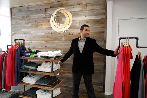 (AP Photo/Marcio Jose Sanchez). In this Dec. 29, 2017, photo, Khalil Moutawakkil, co-founder and CEO of KindPeoples, arranges a clothing line for sale in his marijuana dispensary store in Santa Cruz, Calif.