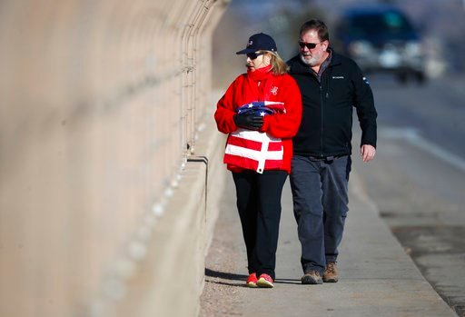 (AP Photo/David Zalubowski). An unidentified couple carry an American flag to hang on the overpass of Colorado Boulevard over Highway C470 before a procession passes with the body of a sheriff's deputy shot and killed while responding to a call Sunday.