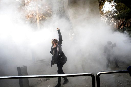 (AP Photo, File). FILE - In this Saturday, Dec. 30, 2017 file photo taken by an individual not employed by the Associated Press and obtained by the AP outside Iran, a university student attends a protest inside Tehran University while a smoke grenade i...
