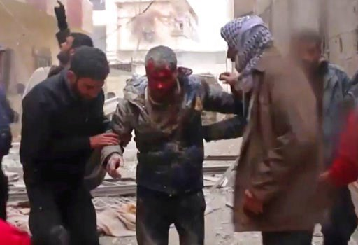 (Syrian Civil Defense, via AP). In this frame grab from video released Monday Jan. 1, 2018 by the Syrian Civil Defense group, known as the White Helmets, Syrians help an injured man on a stretcher after an airstrike hit the Damascus suburb of Masraba, ...