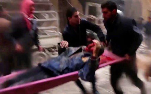 (Syrian Civil Defense, via AP). In this frame grab from video released Monday Jan. 1, 2018 by the Syrian Civil Defense group, known as the White Helmets, Syrians carry an injured man on a stretcher after an airstrike hit the Damascus suburb of Masraba,...