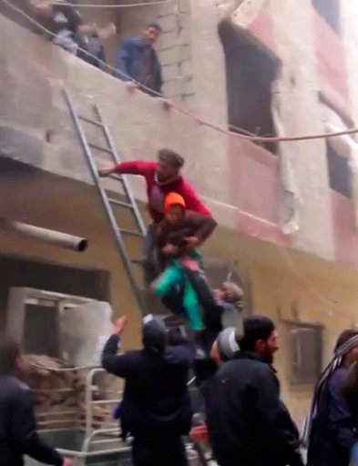 (Syrian Civil Defense, via AP). In this frame grab from video released Monday Jan. 1, 2018 by the Syrian Civil Defense group, known as the White Helmets, Syrians evacuate a boy from a building by using a ladder after an airstrike hit the Damascus subur...