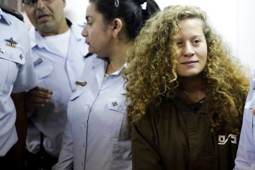 (AP Photo/Mahmoud Illean, File). File - In this Thursday, Dec. 28, 2017 file photo, Ahed Tamimi is brought to a courtroom inside Ofer military prison near Jerusalem. Tamimi, 16, from the village of Nebi Saleh on Monday for attacking the soldiers as wel...