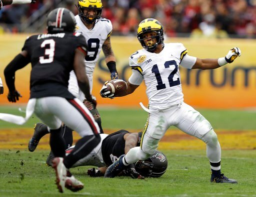 (AP Photo/Chris O'Meara). Michigan running back Chris Evans (12) gets tripped up by South Carolina defensive lineman D.J. Wonnum (8) as defensive back Chris Lammons (3) closes in during the first half of the Outback Bowl NCAA college football game Mond...