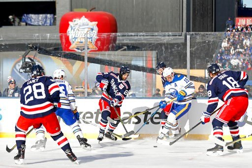 (AP Photo/Adam Hunger). New York Rangers center Boo Nieves (24) passes the puck past Buffalo Sabres center Jack Eichel (15) in the first period of the NHL Winter Classic hockey game at CitiField in New York on Monday, Jan. 1, 2018.