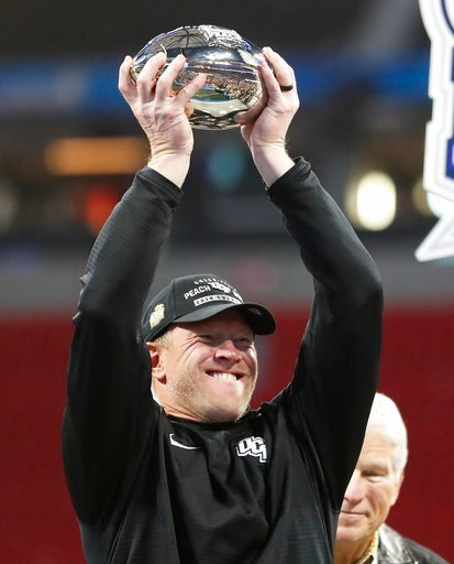 (AP Photo/John Bazemore). Central Florida head coach Scott Frost holds the championship trophy after the Peach Bowl NCAA college football game against Auburn, Monday, Jan. 1, 2018, in Atlanta. Central Florida won 34-27.