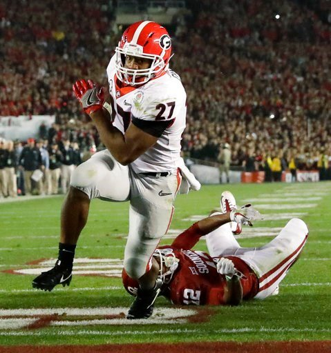 (AP Photo/Gregory Bull). Georgia running back Nick Chubb (27) gets past Oklahoma defensive back Will Johnson (12) to run for a touchdown late in the second half of the Rose Bowl NCAA college football game, Monday, Jan. 1, 2018, in Pasadena, Calif.