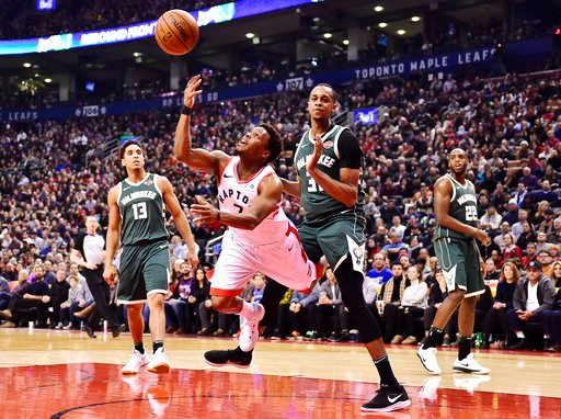 (Frank Gunn/The Canadian Press via AP). Toronto Raptors guard Kyle Lowry (7) throws up a shot as he is fouled by Milwaukee Bucks forward John Henson (31) during first half NBA basketball action in Toronto on Monday, Jan. 1, 2018.