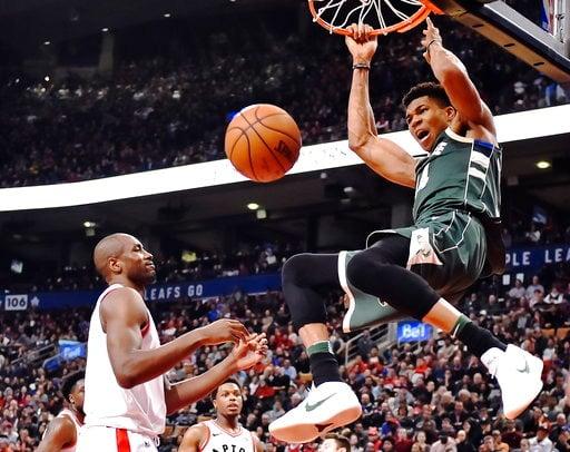 (Frank Gunn/The Canadian Press via AP). Milwaukee Bucks forward Giannis Antetokounmpo (34) dunks as Toronto Raptors forward Serge Ibaka (9) looks on during the second half of an NBA basketball game in Toronto on Monday, Jan. 1, 2018.