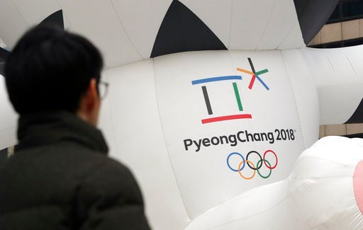 (AP Photo/Lee Jin-man). In this Dec. 29, 2017, photo, a man walks by the official emblem of the 2018 Pyeongchang Olympic Winter Games, in downtown Seoul, South Korea.