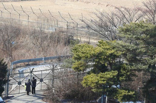 (AP Photo/Lee Jin-man). Visitors stand near the military wire fence at the Imjingak Pavilion in Paju, South Korea, Monday, Jan. 1, 2018.