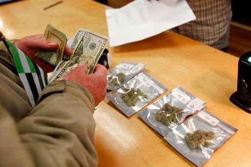 (AP Photo/Mathew Sumner). A customer purchases marijuana at Harborside marijuana dispensary, Monday, Jan. 1, 2018, in Oakland, Calif. Starting New Year's Day, recreational marijuana can be sold legally in California.