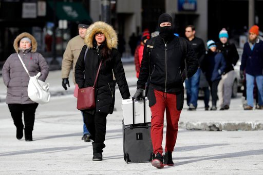 (AP Photo/Nam Y. Huh). Pedestrians are bundled up against frigid temperatures, Sunday, Dec. 31, 2017, in Chicago.