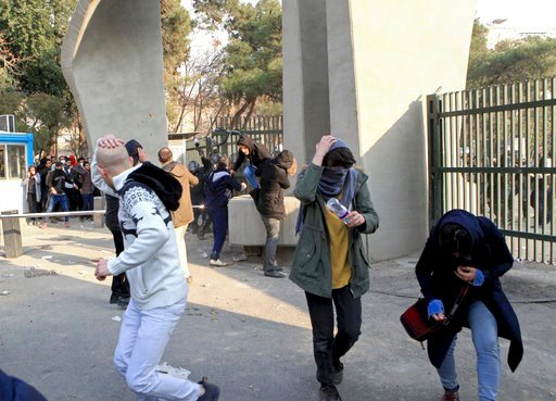 (AP Photo). In this photo taken on Saturday, Dec. 30, 2017, by an individual not employed by the Associated Press and obtained by the AP outside Iran, university students run away from stones thrown by police during an anti-government protest inside Te...