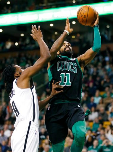 (AP Photo/Michael Dwyer). Boston Celtics' Kyrie Irving (11) shoots in front of Brooklyn Nets' DeMarre Carroll (9) during the third quarter of an NBA basketball game in Boston, Sunday, Dec. 31, 2017.