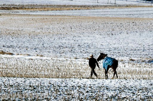 (AP Photo/Matt Rourke). A farmer walks his horse across a baron field in freezing temperatures in Strasburg, Pa., Tuesday, Jan. 2, 2018.