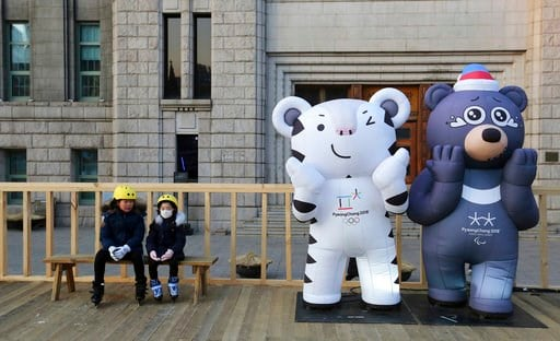 (AP Photo/Ahn Young-joon). Children sit next to the 2018 Pyeongchang Winter Olympic Games' official mascots, a white tiger Soohorang, for the Olympics, and black bear Bandabi, right, for Paralympics, near Seoul Plaza Ice Rink in Seoul, South Korea, Tue...