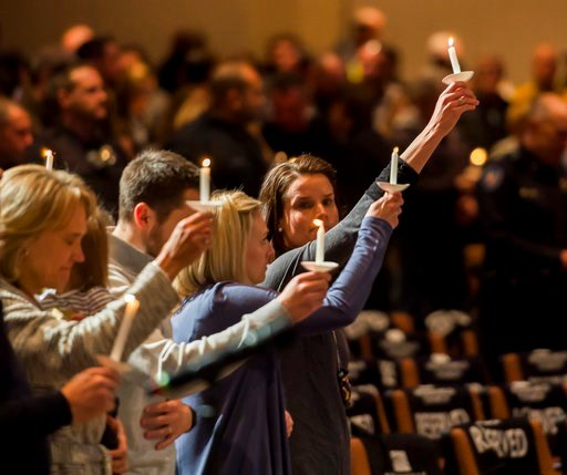 (Dougal Brownlie/The Gazette via AP). Gracie Parrish, center, holds a candle for her late husband Zackari Parrish, a Douglas County deputy, at Mission Hills Church in Littleton, Colo., Monday, Jan. 1, 2018.