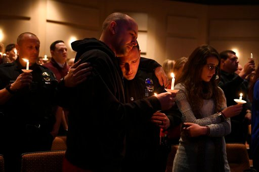 (Helen H. Richardson/The Denver Post via AP). Elizabeth police officer Sean Bigler, middle, gets a hug from a fellow officer during a candle light vigil for their friend and fellow officer Douglas County deputy Zackari Parrish.