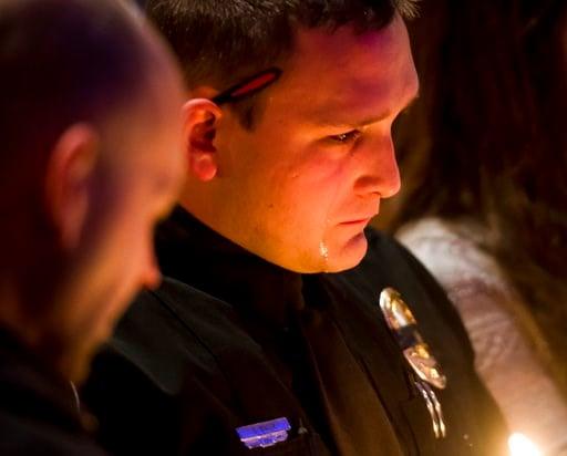 (Dougal Brownlie/The Gazette via AP). Officer Sean R. Bigler reacts during a candlelight vigil at Mission Hills Church on Monday, Jan. 1, 2018, for Deputy Zackari Parrish, 29, in Littleton, Colorado.
