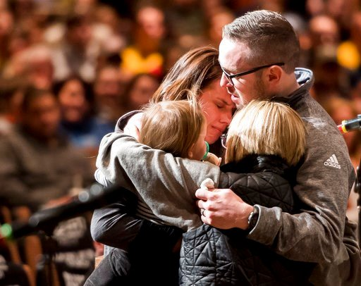 (Dougal Brownlie/The Gazette via AP). Gracie Zacakri, left, is embraced by her small group as family, friends, and community attended a remembrance and candlelight vigil for Deputy Zackari Parrish at Mission Hills Church in Littleton, Colo.