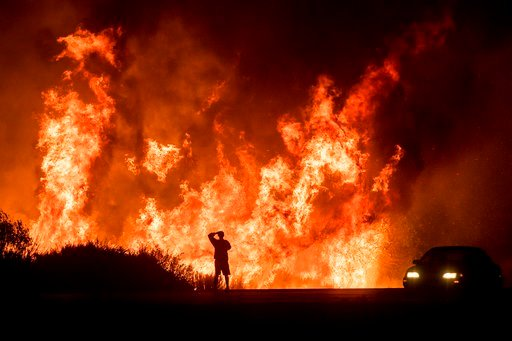 (AP Photo/Noah Berger, File). In this Dec. 6, 2017, file photo, a motorists on Highway 101 watches flames from the Thomas fire leap above the roadway north of Ventura, Calif.
