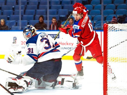 (Nathan Denette/The Canadian Press via AP). United States goaltender Joseph Woll (31) makes save as Russia forward Andrei Altybarmakyan (16) drives the net during the first period of a quarterfinal in the IIHF world junior hockey championships in Buffa...