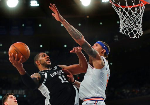 (AP Photo/Julie Jacobson). San Antonio Spurs forward LaMarcus Aldridge (12) puts up a shot against New York Knicks forward Michael Beasley (8) during the third quarter of an NBA basketball game, Tuesday, Jan. 2, 2018, in New York. The Spurs won 100-91.
