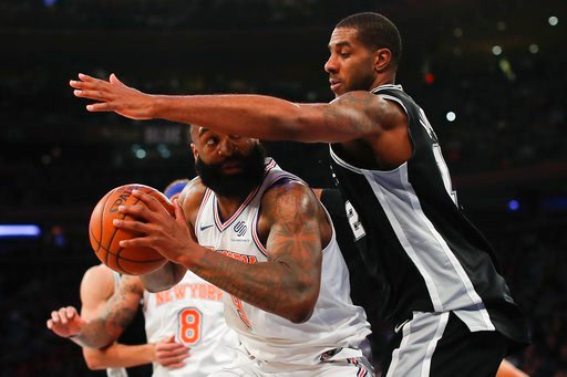 (AP Photo/Julie Jacobson). New York Knicks center Kyle O'Quinn (9) looks to shoot against San Antonio Spurs forward LaMarcus Aldridge (12) during the second quarter of an NBA basketball game, Tuesday, Jan. 2, 2018, in New York.