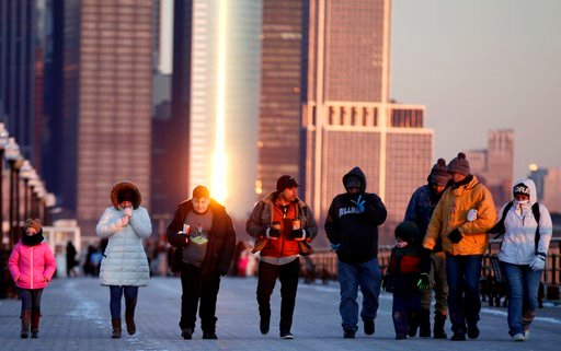 (AP Photo/Julio Cortez). People are bundled up after walking off the Statue of Liberty ferry on a frigid evening at Liberty State Park, Tuesday, Jan. 2, 2018, in Jersey City, N.J.