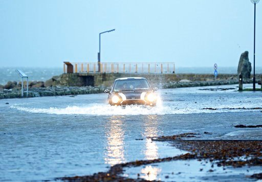 (Brian Lawless/PA via AP). A car drives through a flooded car park in Salthill, Galway, Ireland Wednesday Jan. 3, 2018 as Storm Eleanor lashed Britain and Ireland with violent storm-force winds of up to 100mph, leaving thousands of homes without power ...