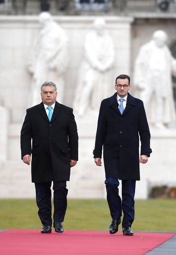 (Tamas Kovacs/MTI via AP). Staying on an official visit in Hungary new Polish Prime Minister Mateusz Morawiecki, right, and his Hungarian counterpart Viktor Orban walk on the red carpet during the welcoming ceremony in front of the Parliament building ...