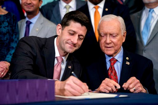 (AP Photo/Andrew Harnik, File). FILE - In this Dec. 21, 2017, file photo, Speaker of the House Paul Ryan, R-Wis., center, accompanied by Senate Finance Committee Chairman Orrin Hatch, R-Utah, right, signs the final version of the GOP tax bill during an...
