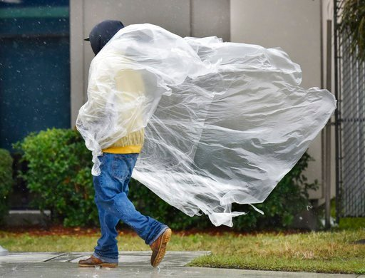 (Will Dickey/The Florida Times-Union via AP). A pedestrian's makeshift raincoat blows in the rainy cold weather Wednesday, Jan. 3, 2018, along Philips Highway in Jacksonville, Fla. A hard freeze with possible icy roads is predicted overnight.