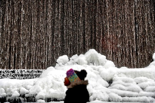 (AP Photo/David Goldman). Alora Freeman, 8, watches as ice builds along a downtown water fountain in Atlanta, Wednesday, Jan. 3, 2018. A brutal winter storm scattered a wintry mix of snow, sleet and freezing rain from normally balmy north Florida up th...