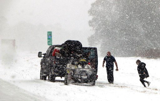(AP Photo/Robert Ray). People attend to their vehicle on Interstate 26, near Savannah, Ga., Wednesday, Jan. 3, 2018. A brutal winter storm dumped snow in Tallahassee, Fla., on Wednesday for the first time in nearly three decades before slogging up the ...