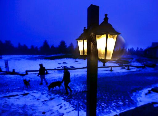 (AP Photo/Michael Probst). Two people walk their dogs on top of the Feldberg mountain near Frankfurt, Germany, as it gets dark on a stormy Wednesday, Jan. 3, 2018.