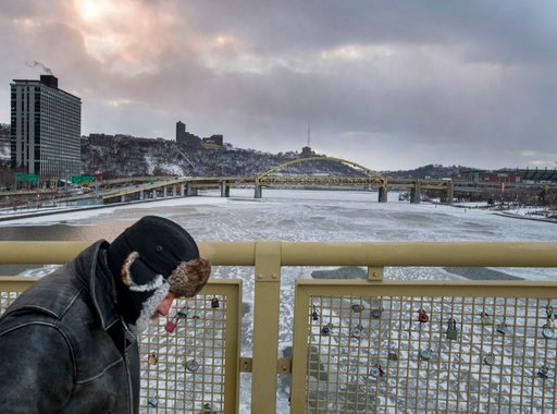 (Steph Chambers/Pittsburgh Post-Gazette via AP). Joe McGowan of Ambridge leans into the wind as he makes his way over the Roberto Clemente Bridge on Thursday, Jan. 4, 2018, in Pittsburgh.