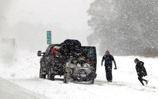 (AP Photo/Robert Ray). People attend to their vehicle on Interstate 16, near Savannah, Ga., Wednesday, Jan. 3, 2018.