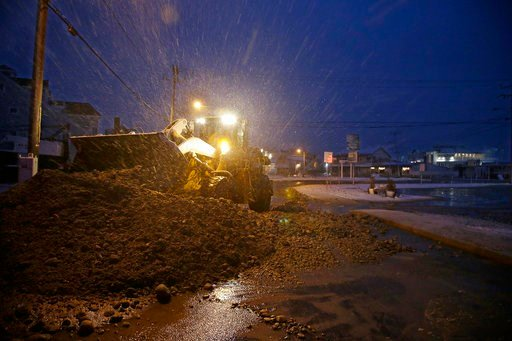 (AP Photo/Stephan Savoia). A bulldozer removes storm debris piling it on a street near the flooded Green Harbor commercial area Thursday, Jan. 4, 2018, in Marshfield, Mass.