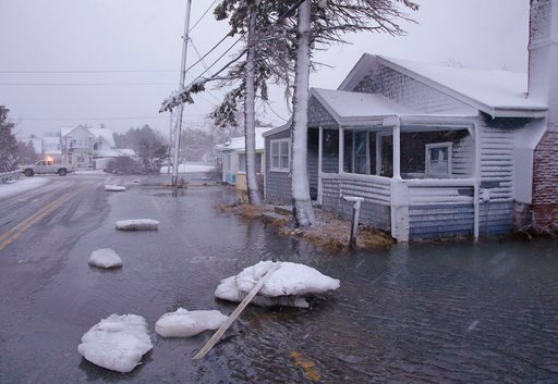 (AP Photo/Stephan Savoia). Large chunks of sea ice strewn Ferry Street in front of a flooded house as a utilities truck passes through a nearby intersection Thursday, Jan. 4, 2018, in Marshfield, Mass.