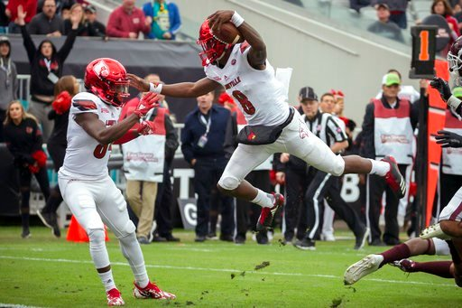 (AP Photo/Stephen B. Morton). Louisville quarterback Lamar Jackson (8) jumps over a Mississippi State defender before scoring a touchdown during the first half of the TaxSlayer Bowl NCAA college football game, Saturday, Dec. 30, 2017, in Jacksonville, ...